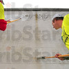 "Tribune-Star/Joseph C. Garza<br /> They have it covered: Indiana State University seniors Justin Cox of Sheridan and Ryan Wildeman of Evansville paint over graffiti on Ace Washer off of south Eighth Street as part of an effort to ""wipe out"" graffiti Saturday around the city."
