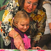 Tribune-Star/Joseph C. Garza<br /> Helping hands: Franklin Elementary School kindergartner Maylee Brown stamps her hand on a banner with help from Dr. Ferial Alsikafi Wednesday at the Terre Haute Children's Museum as part of S.A.V.E. Day.