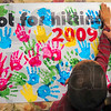 Tribune-Star/Joseph C. Garza<br /> They're for hugging or holding hands: Dr. Ferial Alsikafi helps a youngster stamp his hand on a Hands Are Not For Hitting Banner Wednesday at the Terre Haute Children's Museum as part of S.A.V.E. Day.