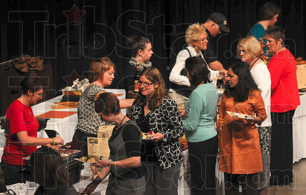 Tribune-Star/Joseph C. Garza<br /> Food power: Attendees of the United Way of the Wabash Valley's Power of the Purse fundraiser sample the various foods available before the auction Wednesday at Hulman Center.