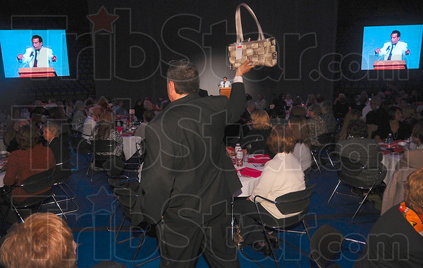 Tribune-Star/Joseph C. Garza<br /> The next item up for bid...: Duke Energy's Rick Burger displays an item up for bid as he walks through the tables at the Power of the Purse fundraising event Wednesday at Hulman Center.