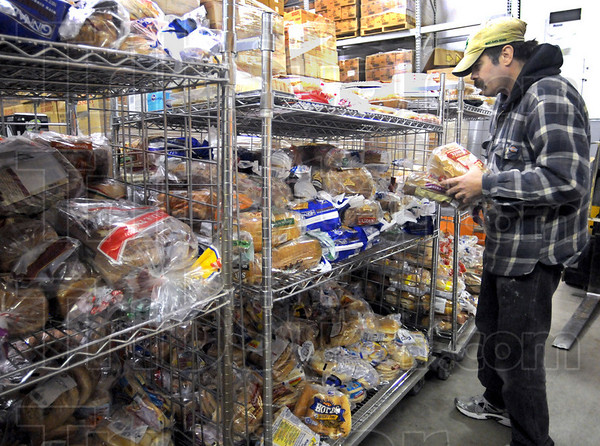 Bread bin: Catholic Charities employee Terry Perdue puts loaves of bread into a storage area at the facility Monday morning.