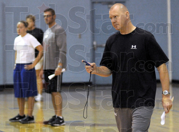 Watchful: Indiana State women's basketball coach Jim Weidie (R) puts the stopwatch on his girls as they run practice drills in the Boy's and Girl's Club gym. At left are assistant coaches Mel Boeglin and Clint Weddle watching the action.
