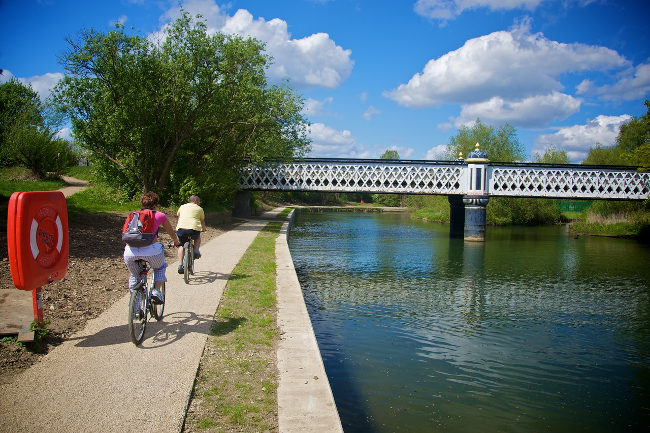 Tourists cycling by the river.