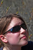 Jess at the belay with the climb reflected in her sunglasses.