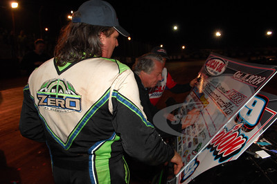 Rome Speedway promoter Mickey Swims signs the Victory Lane check for the race winner and the 2009 Lucas Oil Late Model Dirt Series champion - Scott Bloomquist