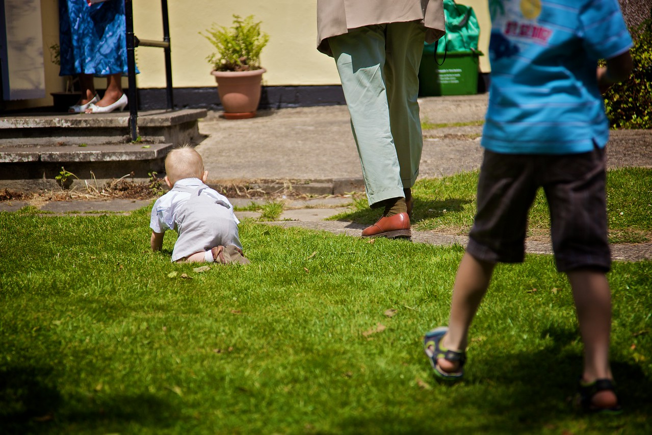 Hugh rapidly crawling away, dodging people's feet as he does so.