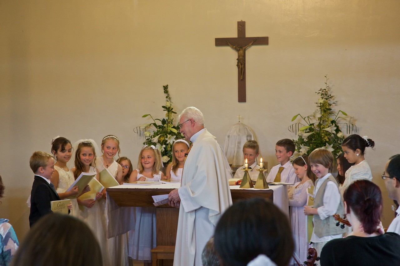 The parish priest addressing First Communicants after Mass.