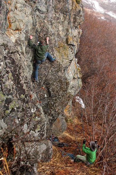 Richard moves higher on the wet rock with Tracy at the belay.
