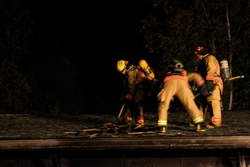 Jess Young, Tim Gonyea, and DJ Angaiak work to get under the shingles and expose portions of the roof still burning after the initial fire attack.