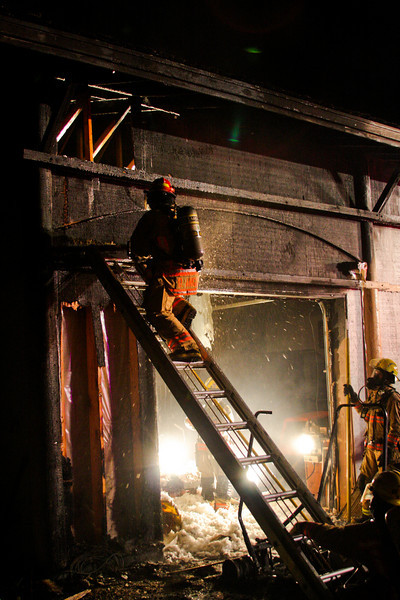 Scene lighting gives firefighters a bit of help in the late night darkness as DJ Angaiak works to open up a wall with heat inside.