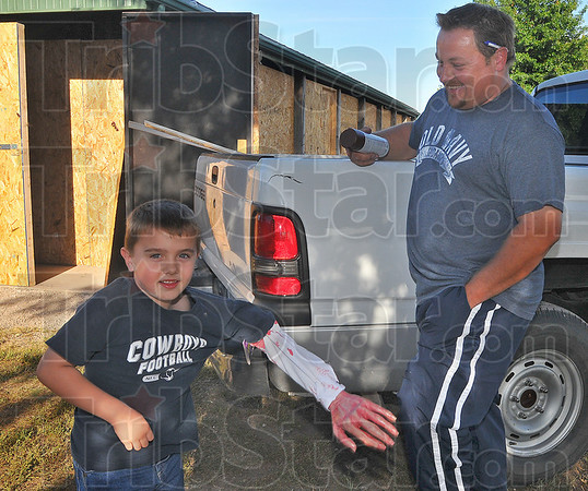 Helping hand: Dawson Hoopingarner brings a smile to his dad Paco's face has he plays with one of the props for the Terre Town baseball haunted house.