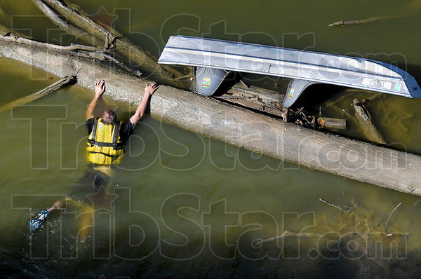 Victim: An actor holds onto a log in the Wabash River Thursday afternoon  as film crews make a documentary film on the First Response Team of America's hovercraft operations.