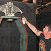 Finishing touches: Dusty Coffey paints a coffin in the haunted house that will be a fundraiser for the Terre Town baseball league.