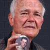 Then & now: Tom Roberts holds a button with his portrait taken as a 19 year-old second lieutenant in 1944.