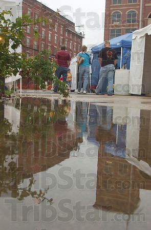 Soggy start: Visitors to the Terre Haute Street Fair walk past the stalls of the Crossroads ArtsFest Thursday evening. Light rain left puddles standing in streets and parkinglots and along sidewalks.