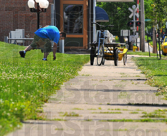 Alittle more: Matt Wycoff collects anothe can from tha lawn along north 7th street just north of the ISU campus.