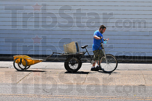Transportation: Matt Wycoff uses an adult tricycle with a jerry-built deck for hauling larger items. Behind this he has attached a converted child carrier for his scrap metal.