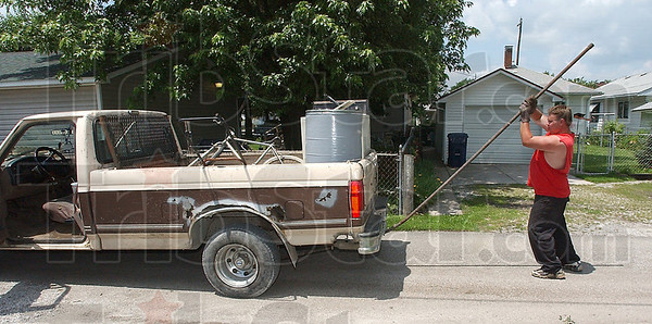 Multi purpose vehicle: Charles Farner bends a length of pipe to more easily fit it into the bed of his truck.