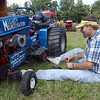 Tribune-Star/Jim Avelis<br /> Hard at play: Bill Flowers adds weight to his competition lawn and garden tractor before a contest at the Fontanet bean dinner last month.