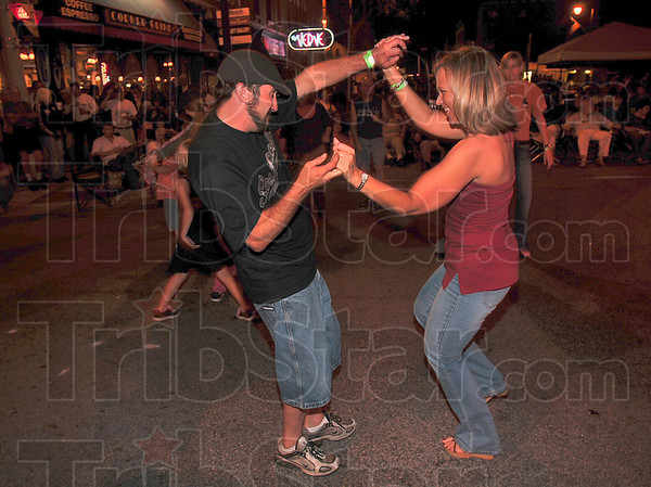 Tribune-Star/Joseph C. Garza<br /> Not feeling too blue: Blues at the Crossroads fans Brent Hamblen and Robin Wilson dance the night away to sounds of Mike Milligan and Steam Shovel Friday downtown.