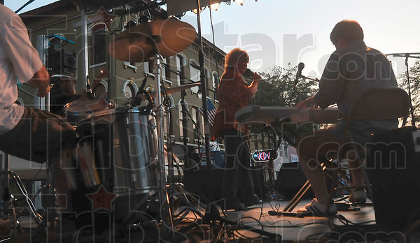 Tribune-Star/Joseph C. Garza<br /> Sunset blues: Singer Jill Shutt is nearly silhouetted by Friday's setting sun during her performance at Blues at the Crossroads on Wabash Avenue.