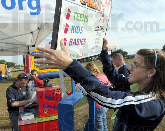 """Open for business: Wendy Runyon-Ricker puts the """"open"""" sign out as they prepare to make ID cards for kids at the Anderson Chiropractic Kid's Day event."""