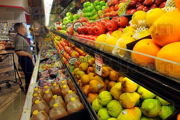 High quality: Karl Zucker looks over apples in the fresh fruit section of Baesler's Market.