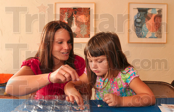 Tribune-Star/Joseph C. Garza<br /> Working together: Four-year-old Josalyn Huxford, right, and her mother, Jacquie Huxford, work together to create a bead bracelet during an Art Totality event Saturday, Aug. 29 at Gopalan Art Gallery.