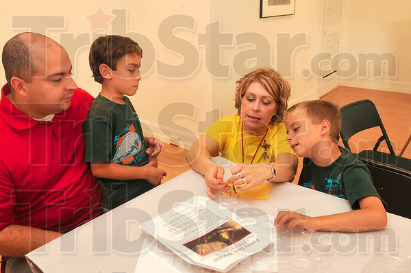Tribune-Star/Joseph C. Garza<br /> Family project: Stacey Thacker, Art Totality founding member, shows John Ford and his two sons, Matthew, 7, and Samuel, 7, how to create a bracelet for their mother during an Art Totality event Saturday, Aug. 29 at Gopalan Art Gallery.