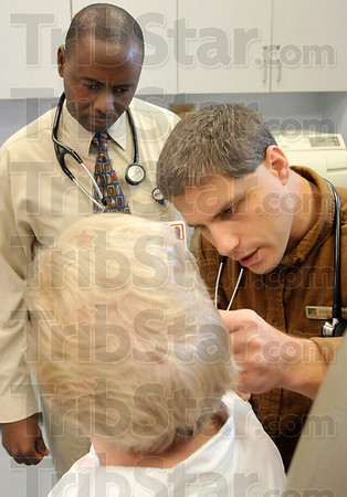 Tribune-Star/Joseph C. Garza<br /> Rural medicine at work: Dr. Eric Beachy, right, of the Clay City Center for Family Medicine examines the ear of patient Joyce Nees as third year family medicine resident Kenneth Kigorwe looks on Friday, Dec. 5, 2008 at the center. Kigorwe is in the Union Hospital Family Medicine Residency Program and will become a rural health care physician.