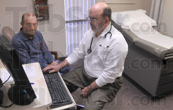 Tribune-Star/Joseph C. Garza<br /> Taking care of his hometown: Dr. Steven Macke, a Marshall, Ill. High School graduate, talks with patient, John Lahman, Thursday, Dec. 4, 2008 at the Cork Medical Center in Marshall. Dr. Macke has practiced medicine in his hometown for 30 years.