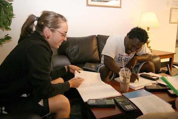 Abby Callahan, senior, and Danaj Seymour, junior, share a joke as they study physics in the HAPY lobby Sunday night.