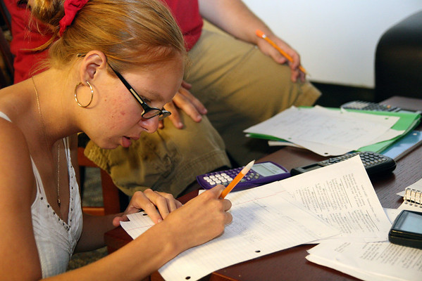 Sarah Bunker, junior, corrects a mistake in her physics homework as she studies with a group of friends Sunday night.