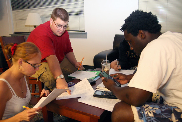 Andy Bridges, junior, helps Sarah Bunker, junior, with an equation as Danaj Seymour, junior, calculates.  The group were studying physics in the HAPY lobby Sunday night.