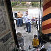 Eats: John Stadler stands on the sidewalk in front of Stadler's Barbershop Monday afternoon sipping a soft drink and having a hotdog. He's taking a break after giving free haircuts to kids under 8th grade level at his family business. Kids and their families were also treated to free food and drinks.