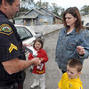 Identification kit: Terre Haute police officer Cpl. Larry Manley gives a child identification kit to Brandy Hauser for her children, Emily and Sean Monday afternoon in the parking lot of Stadler's Barber Shop. The shop is doing free haircuts for kids in the 8th grade and under all day Monday.