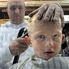 Just a little off the top: John Stadler cuts the hair of eight-year-old Cameron Andrade Monday afternoon. The local barbershop provided free haircuts to those students in the 8th grade and below all day Monday.