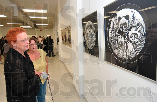 Tribune-Star/Joseph C. Garza<br /> Art and you: Nancy and Gil Crews take a closer look at the work on display at the Halcyon during First Friday, Friday, Sept. 4.