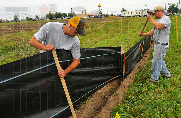 Prep work: Darin Phillips and Jeremy Fortner install an erosion control fence along Margaret Avenue near State Road 46 where a new Holiday Inn Express will be built. The hotel will face east, fronting onto Joe Fox Street and sit on about 3 acres of land.