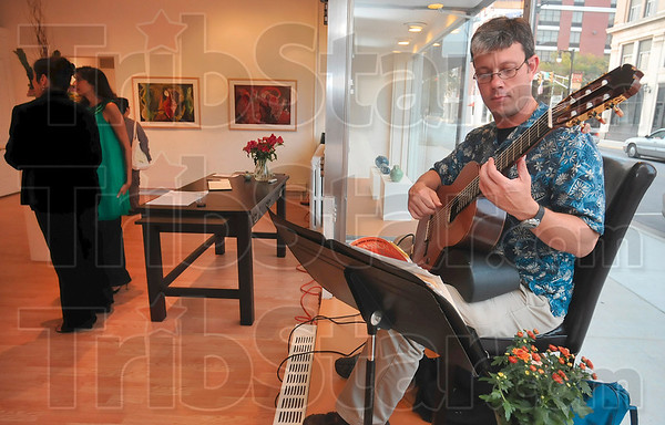 Tribune-Star/Joseph C. Garza<br /> Classical and contemporary: Brent McPike fills the rooms at Gopalan Contemporary Art with the sounds of classical guitar during First Friday at the gallery Friday, Sept. 4 on south Seventh Street.