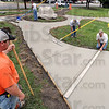 Sidewalk art: A crew of workers from ST Construction finishes the sidewalk leading to and around the Lauren Ewing sculpture in Gilbert Park Wednesday morning.
