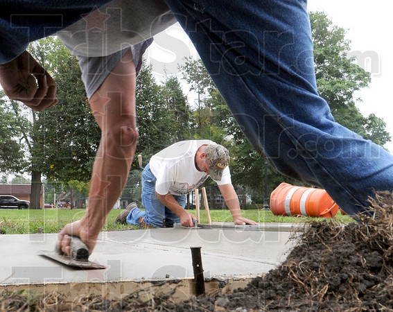 Sidewalk artists: Steve Marietta (center) and Delbert Joy of ST Construction do some finishing work on new concrete in Gilbert Park Wednesday morning.