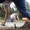 Sidewalk artists: Steve Marietta (center) and Delbert Joy of ST Construction do some finishing work on new concrete in Gilbert Park Wednesday morning.