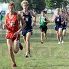 Leaders: Terre Haute North's Milton Brinza eyes the early leader of the Boy's cross-country championship meet Thursday night at Rea Park. He eventually made the pass and went on to win the meet.