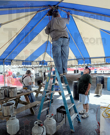 Preparation: Don May installs an overhead light fixture in the cooking tent for the annual Oktoberfest Thursday afternoon.