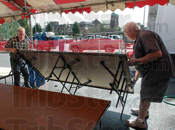 Staged: German Club members Frank Goffinet and David Walbring erect the stage for the annual Oktoberfest Thursday afternoon.