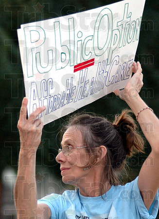 Option: Suzanne Overton holds a sign during Wednesday night's vigil held in support of health care reform.