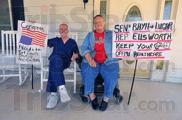 """We're back: Jerry Hawker and his wife Lesile sit on their Farmersburg front porch with the signs they carried in Washington D.C. this past wekend.  Hawker, who read a version of the proposed health care bill at """"Open Congress.org"""" said the parts that say the government committees """"shall"""" do a cost benefit analysis on the aged and sick worry him."""