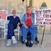 "We're back: Jerry Hawker and his wife Lesile sit on their Farmersburg front porch with the signs they carried in Washington D.C. this past wekend.  Hawker, who read a version of the proposed health care bill at ""Open Congress.org"" said the parts that say the government committees ""shall"" do a cost benefit analysis on the aged and sick worry him."
